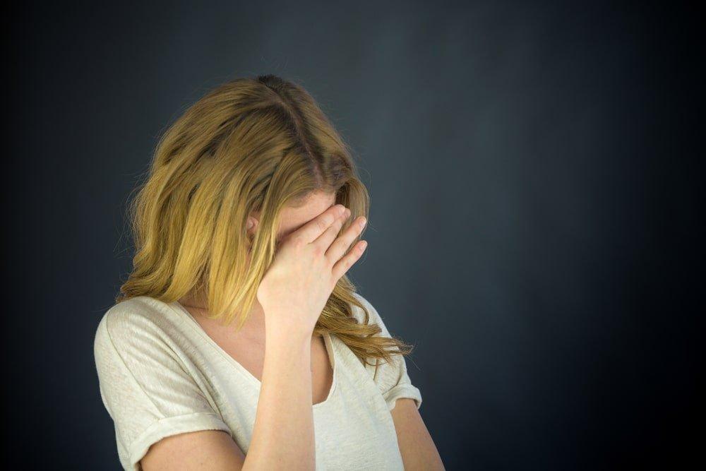 женщина прячет лицо